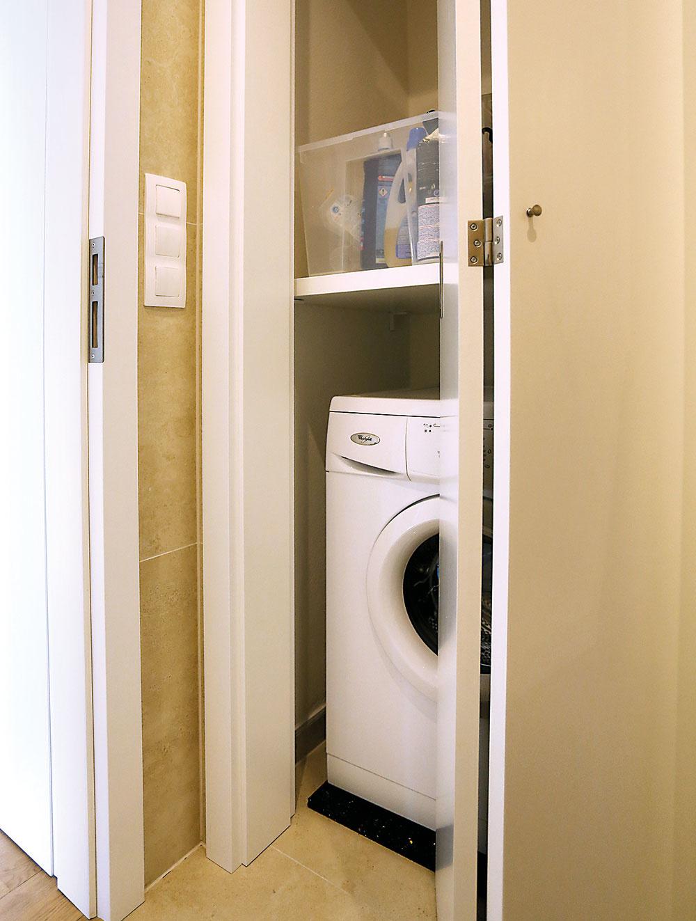 """Práčka """"nestraší"""" v kúpeľni, ale je skrytá za dverami v nike v hosťovskom WC, kde pre ňu architekt vytvoril miniatúrnu """"práčovňu""""."""