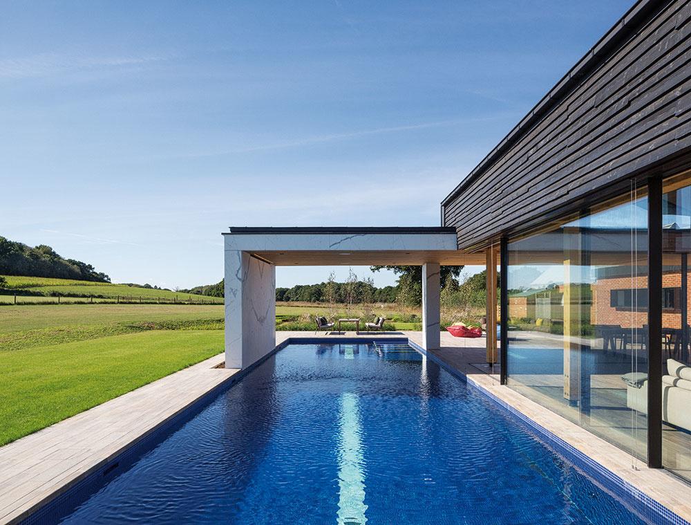 Dlhý bazén lemuje južnú stranu domu. Ak sa odsunie zasklená stena, hranica medzi interiérom a exteriérom zmizne, takže obývačka sa stane súčasťou terasy a otvorenej krajiny.
