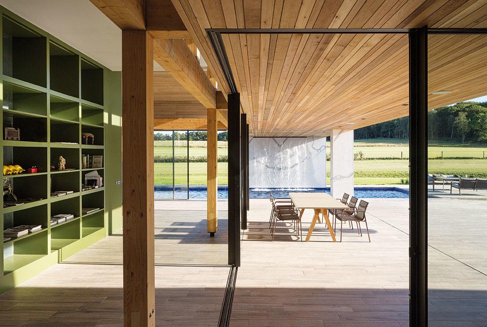 Vonkajšia jedáleň nadväzuje na obývačku aj vnútornú jedáleň. Zastrešenie vonkajšieho priestoru pokračuje vodnou stenou pri bazéne a zároveň podporuje dojem súvislosti s interiérom, vytvára príjemný tieň aj ochranu pre stolujúcich.