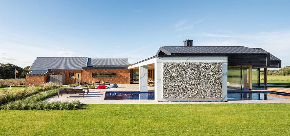 """Pohľad z juhu. Na juh sa otvára chránené vonkajšie nádvorie, zariadené ako pôsobivá """"letná obývačka"""". Zo severnej strany ho chráni tehlový objekt s kuchyňou, jedálňou a garážami, na východe naň nadväzuje zasklená obývačka."""