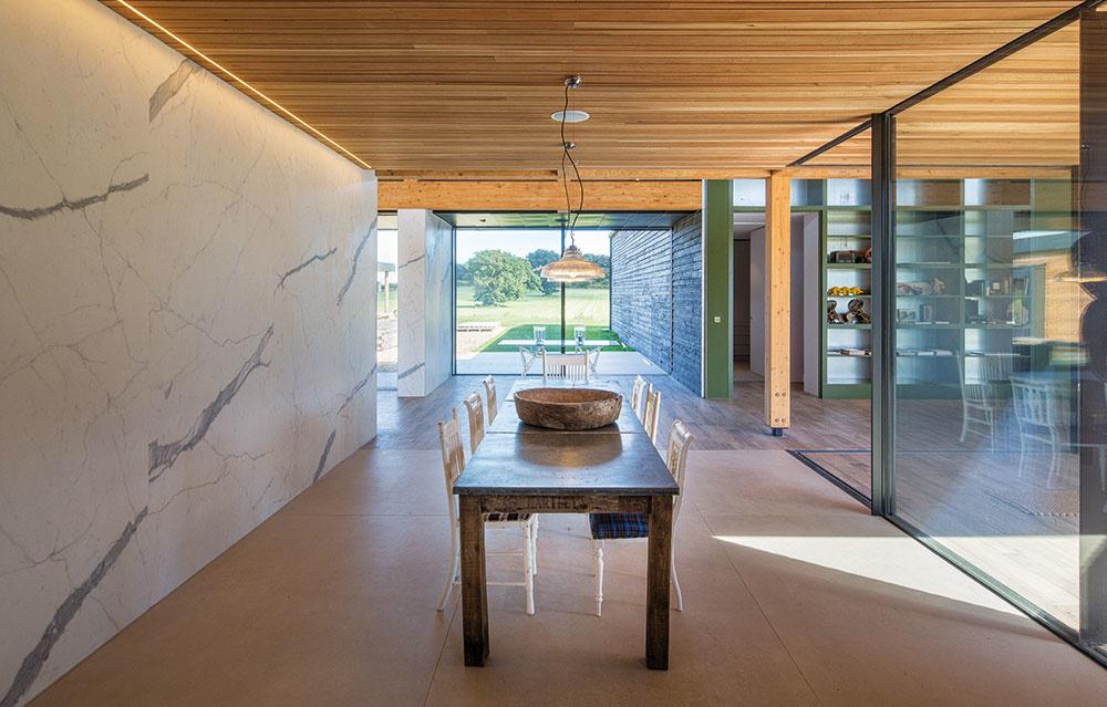 Kombináciu moderného s tradičným nájdeme nielen v exteriéri, ale aj v interiéri domu. K rustikálnym prvkom, aké by sme práve na farme čakali, patrí napríklad veľký drevený stôl so stoličkami v jedálni.