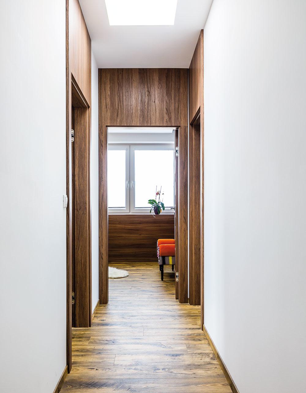 Na všetky dvere nadväzuje obklad siahajúci až po strop. I keď má chodba štandardnú výšku, vďaka svetlovodom a opticky zvýšeným dverám vyzerá vyššia a vzdušnejšia.