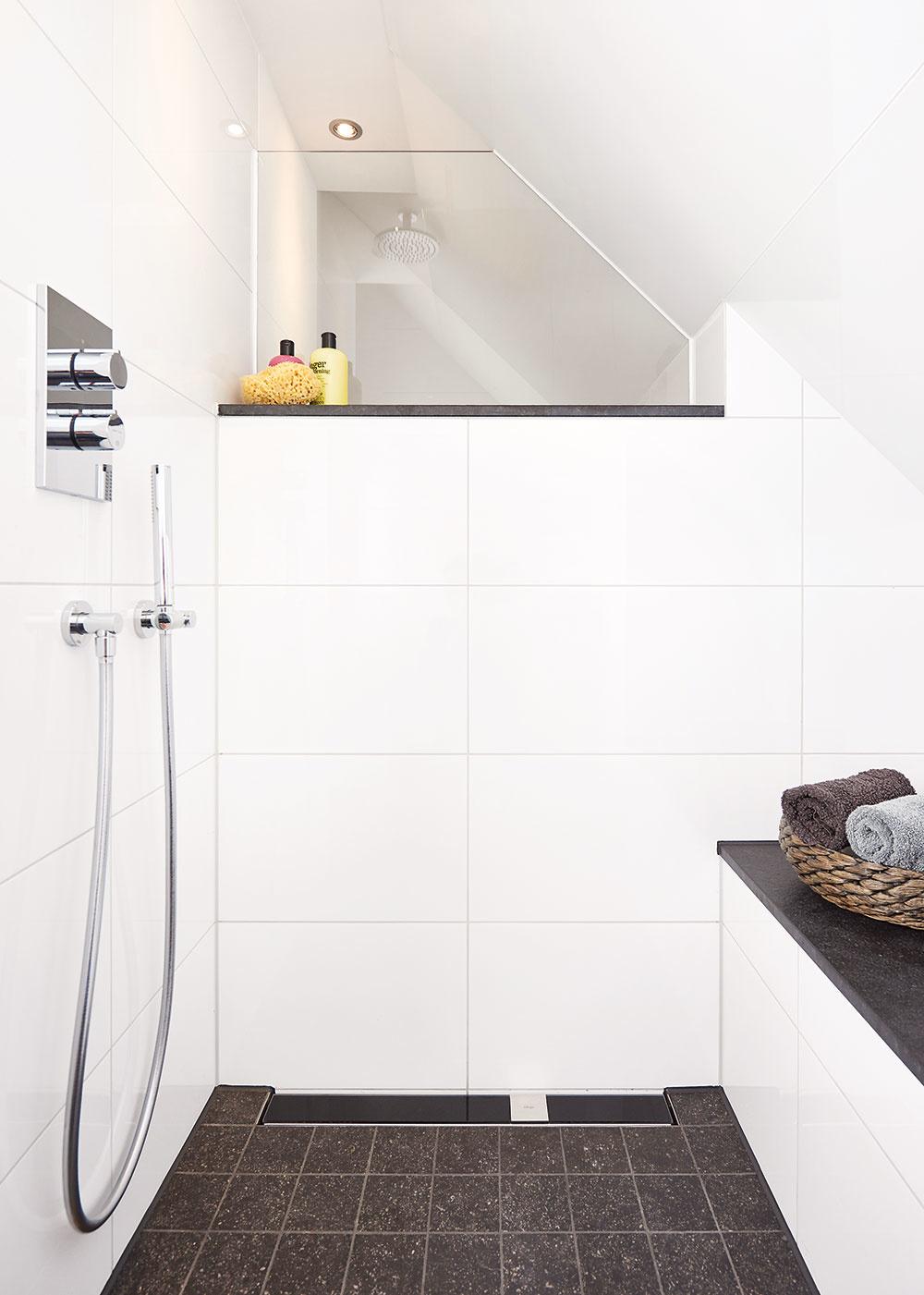 Sprchový kút typu walk-in poskytuje dostatočný priestor a voľnosť pohybu aj v podkrovnej kúpeľni so šikmým stropom. Takéto riešenie navyše kúpeľňu opticky otvorí a vďaka bezprahovému prechodu ho investor ocení aj vo vyššom veku. Jeho súčasťou je aj praktická lavička.