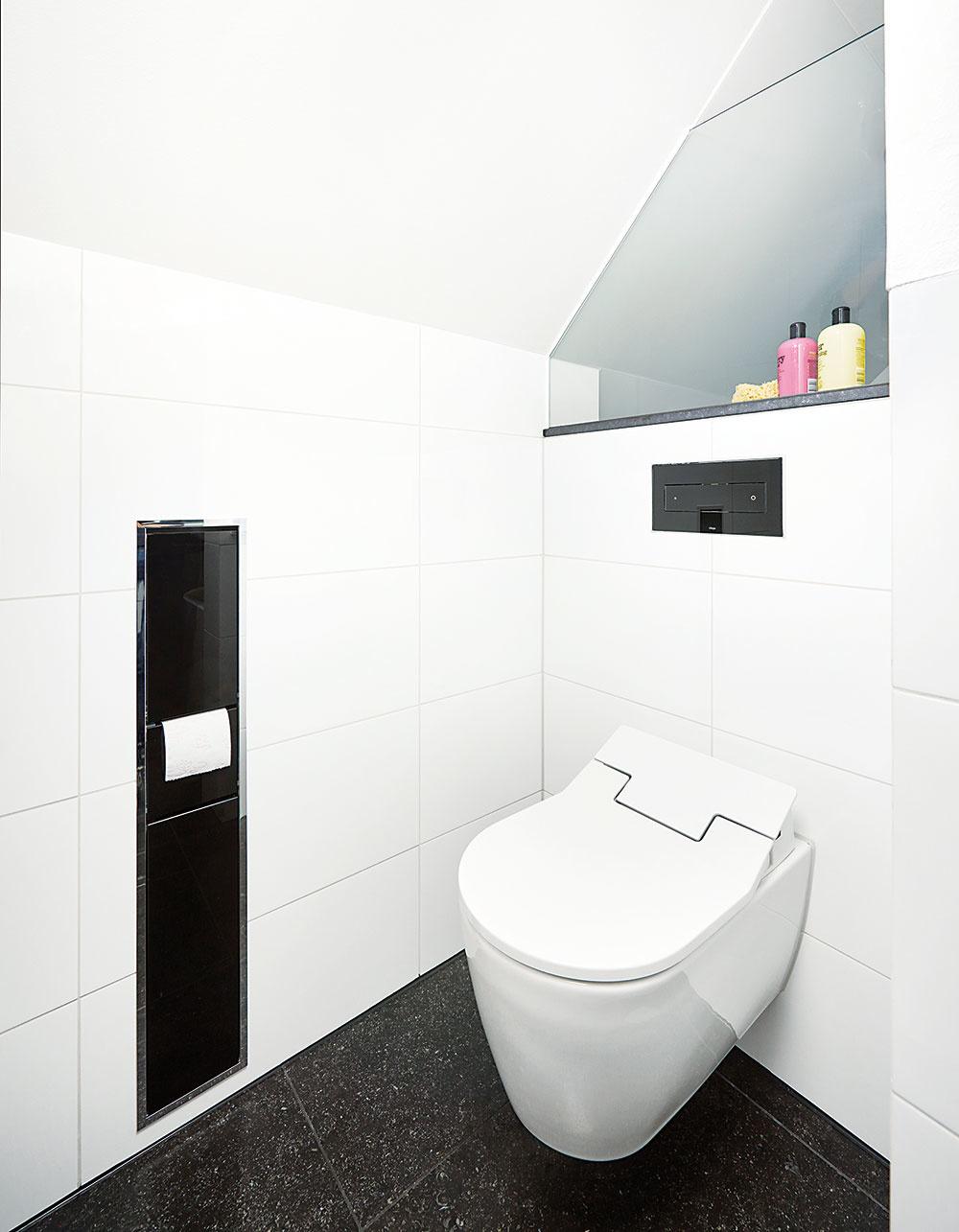 Investor si želal, aby sa aj zariadenie kúpeľne prispôsobilo bielo-čiernej farebnej kombinácii, ktorá je príznačná pre celý interiér rodinného domu. Tá sa objavuje aj v priestore toalety, kde sa nachádza čierne splachovacie WC tlačidlo vsadené do bieleho obkladu.