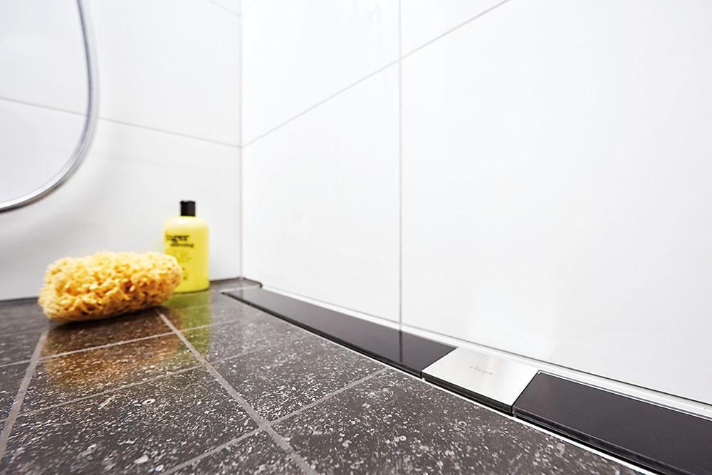 Sprchový žľab je harmonicky začlenený do podlahy. Projektant v tomto prípade zvolil odtok k stene a rám z nehrdzavejúcej ocele s dizajnovým roštom z čierneho bezpečnostného skla.