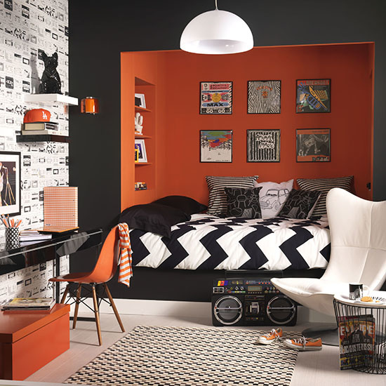 Retro black and orange bedroom, painted black and orange walls, bed built into alcove raised on platform, framed wall mounted album covers, white wing backed chair large ghetto blaster, black gloss desk, wallpaper with cassette tape print, white glass pendant light, IH 08/2012 Pub Orig
