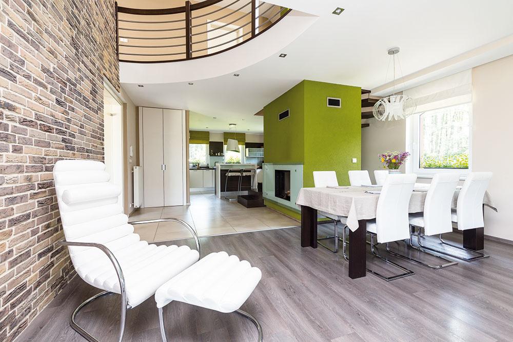 Obývačka prepojená sjedálňou akuchyňou je veľká avzdušná. Vizuálne sú oddelené odlišnou podlahou. Centrom denného priestoru je kozub, okolo ktorého sa vinie schodisko na horné poschodie do pokojnej časti so spálňami. Štýl, ktorý majiteľka zvolila, podčiarkuje aj tehlová stena vzemitých odtieňoch hnedej abéžovej farby.