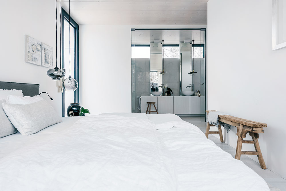 Na poschodí domu sú tri spálne a dve kúpeľne. Z hlavnej spálne je prístupný šatník a kúpeľňa en suite. Dominancia bielej farby dodáva priestorom pocit príjemnej čistoty a zároveň umožňuje odraz svetla, ktoré do interiéru preniká cez koruny stromov okolitého lesa.