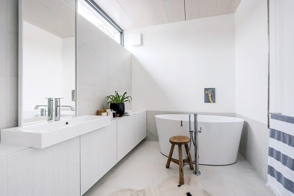 Strohá geometria s pravouhlými líniami nábytku a biely základ interiéru zjednocujú priestory celého domu. V kúpeľniach vytvára teplé, hrubo opracované drevo pôsobivý kontrast k lesklému bielemu mramoru na obkladoch.
