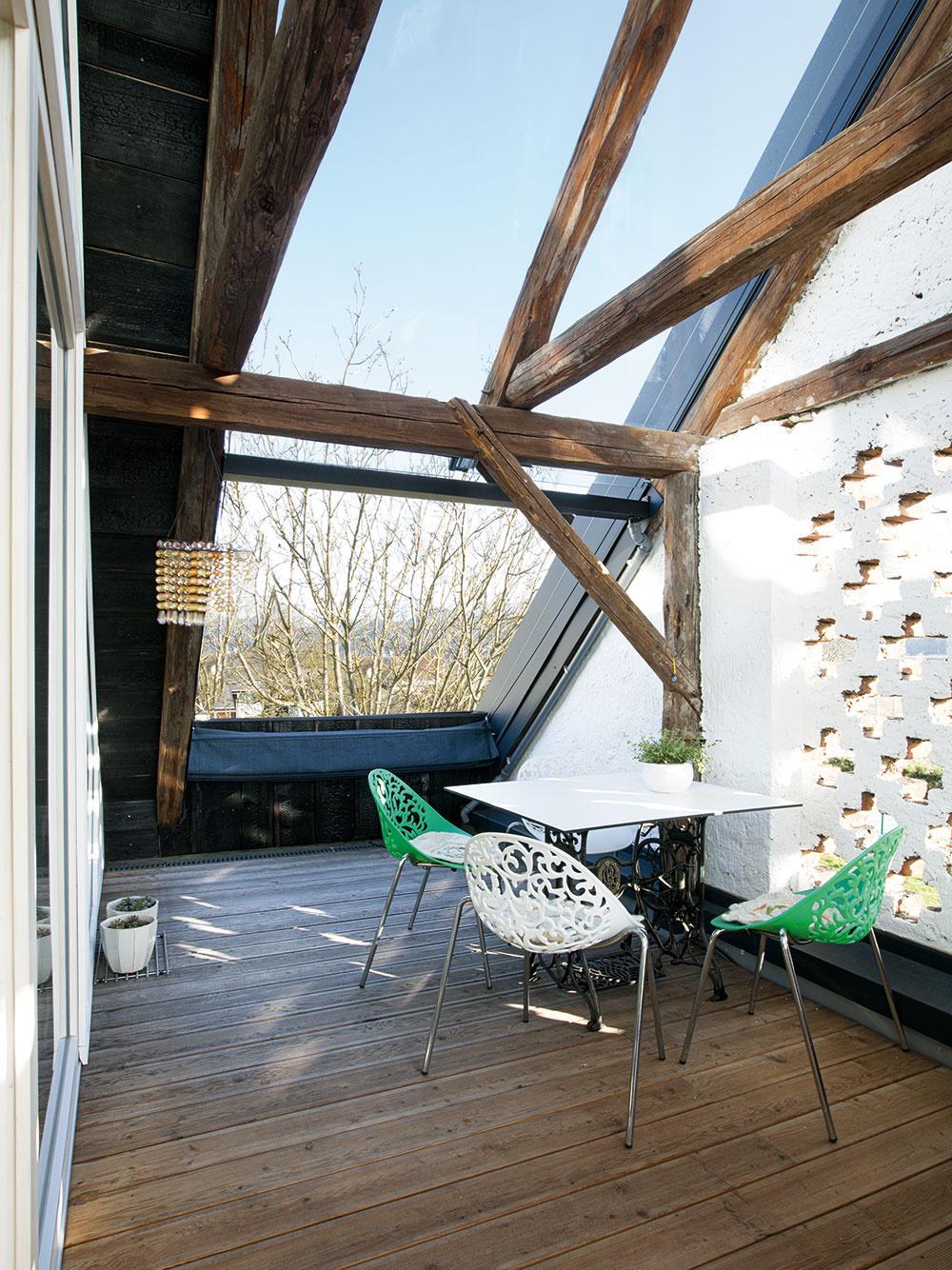 Vonkajší priestor – terasa v južnej časti strechy chránená štítovou stenou – je intenzívne prepojený s obývačkou cez veľkorysú zasklenú stenu siahajúcu až po hrebeň.