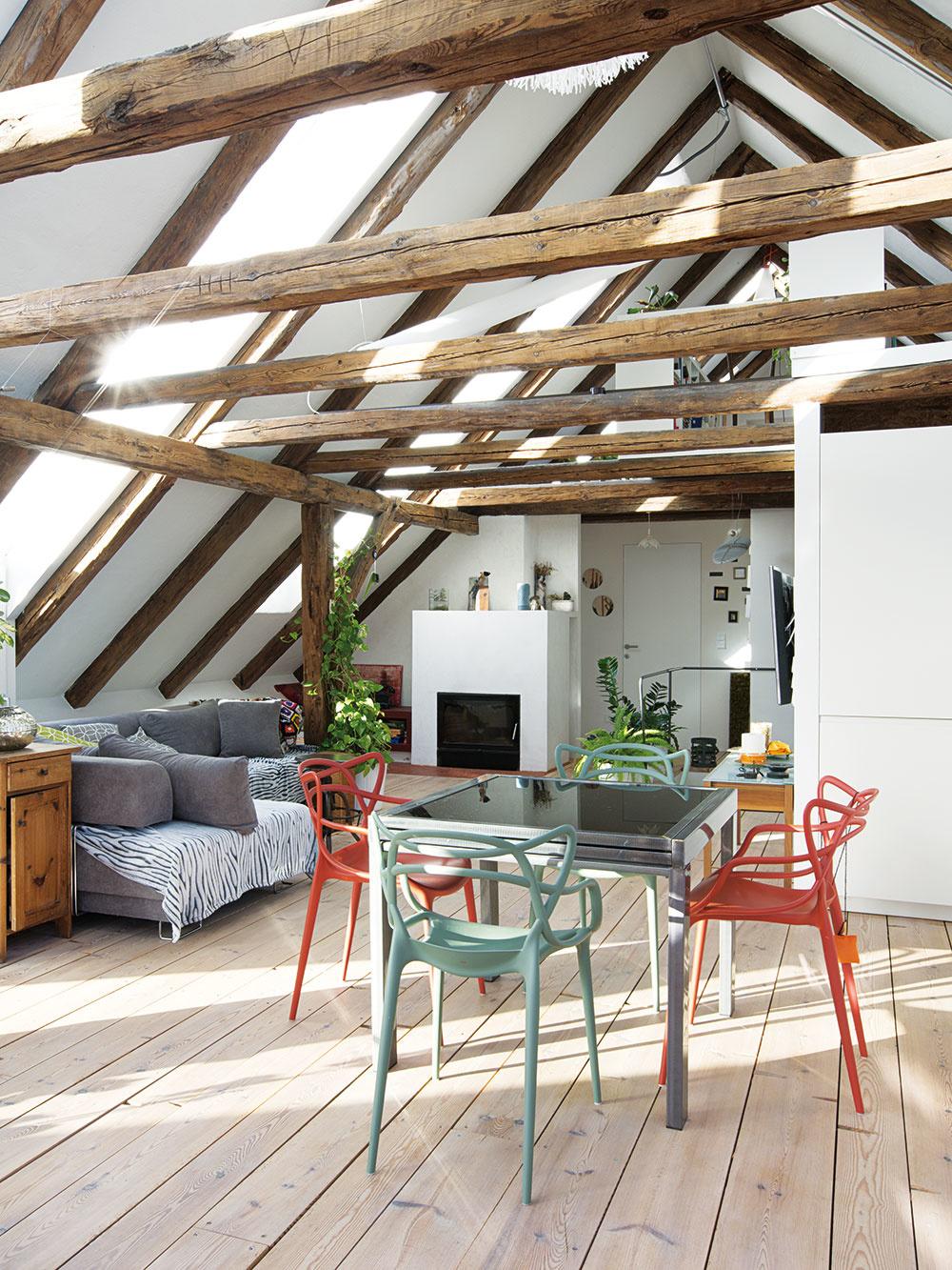K dokonalej atmosfére historického podkrovia prispievajú aj zvolené materiály – popri zachovaných drevených konštrukciách je to aj recyklované drevo na podlahe a tradičné biele omietky.