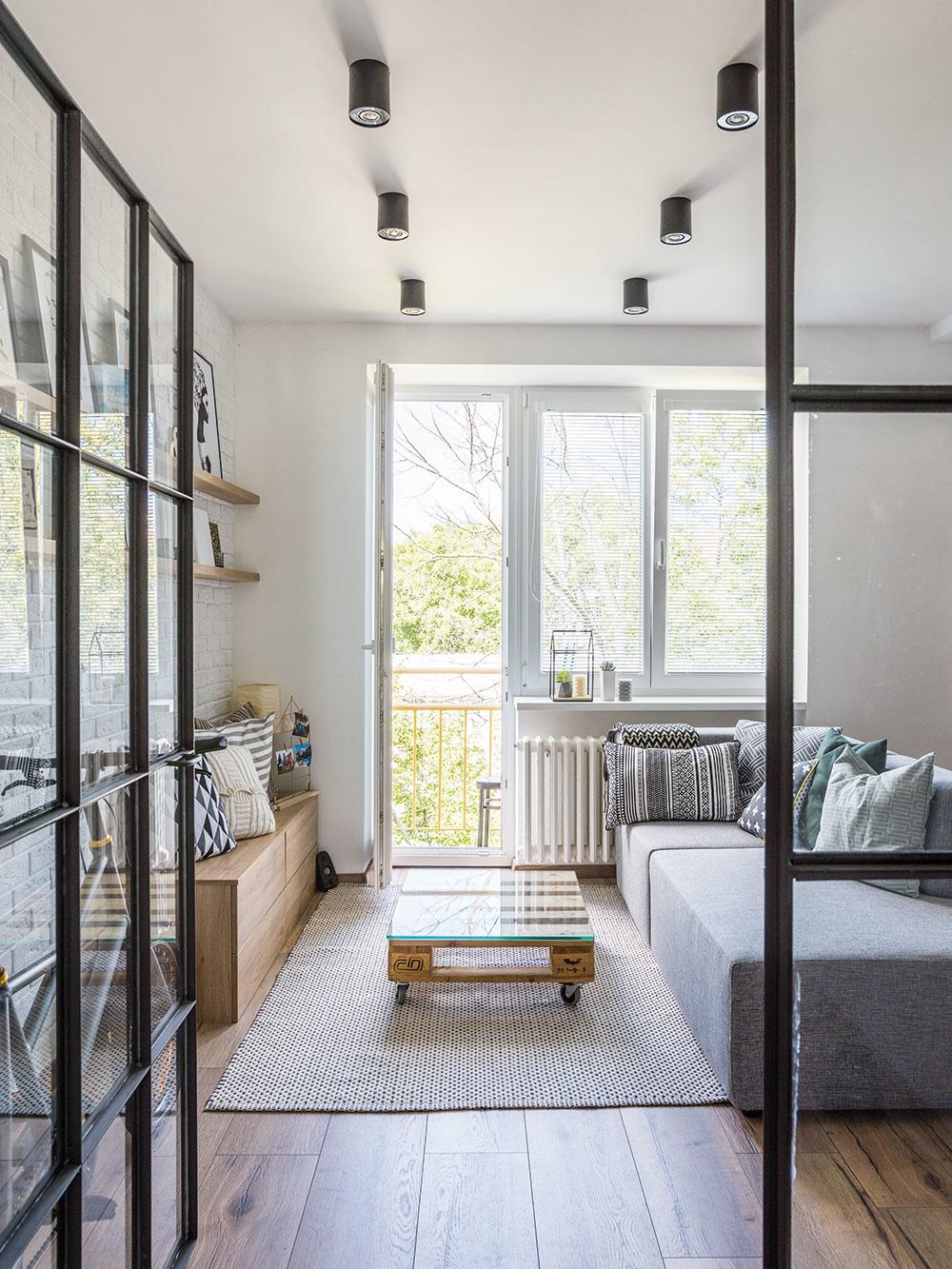 """Nízky paletový stolík so sklenenou doskou podporuje """"surový"""" vzhľad interiéru. Paleta, z ktorej ho vyrobili, pôvodne slúžila Českým dráham."""