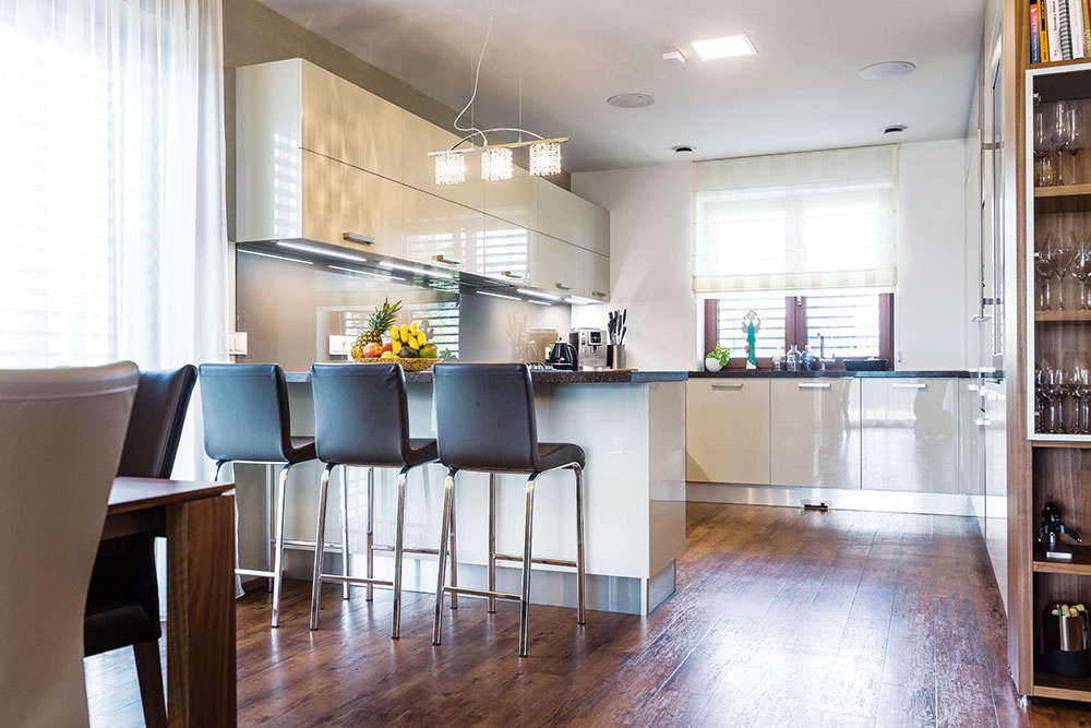 """Kuchyňa tvorí """"záliv"""", na ktorý cez barový pult nadväzuje jedálenský stôl umiestnený v otvorenom dennom priestore. Je tak so zvyškom miestnosti spojená, ale zároveň od nej mierne opticky oddelená."""