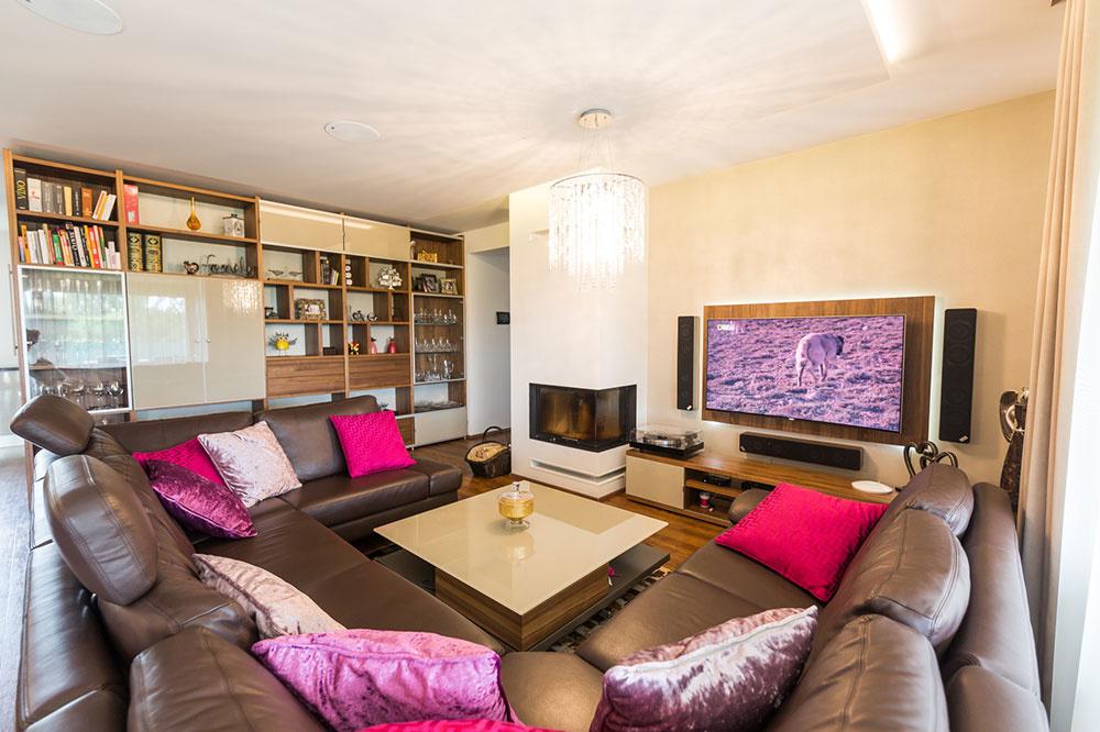 """Veľká """"rodinná sedačka"""" určuje v otvorenom dennom priestore imaginárne hranice obývačky. Atypický kus vyrobili na mieru tak, aby presne sadol do priestoru a splnil požiadavky majiteľov na pohodlie. Na oživenie kombinácie hnedej kože s drevom a odtieňmi béžovej zvolila pani Danka žiarivú cyklámenovú a fialkasté tóny, ktoré sa objavujú na vankúšoch a ďalších textíliách."""