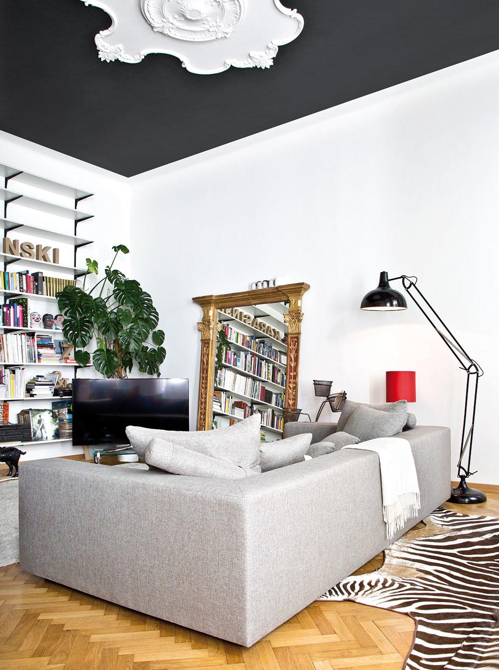 ČIERNY STROP SO ŠTUKOVÝM ZDOBENÍM, zebria koža a starožitný zrkadlový rám sa napriek svojej výraznosti nebijú a vytvárajú v obývačke punc luxusu.