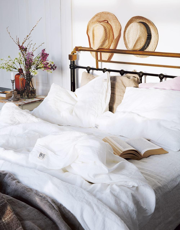 ČARO JEDNODUCHÉHO. Miesto fotografií či obrazov ozdobte stenu slamenými klobúkmi, na nočný stolík položte vázu s kvetmi a periny navlečte do bielych obliečok. A môžete sa začítať do obľúbenej knihy...