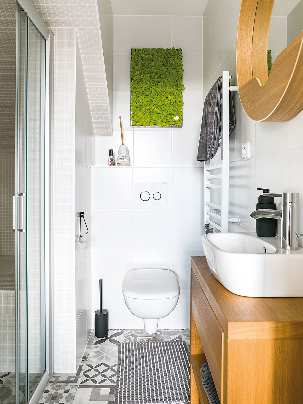 V kúpeľni na prízemí slúžiacej majiteľovi vznikol priestranný sprchový kút. Stenu príjemne dotvára machová dekorácia.