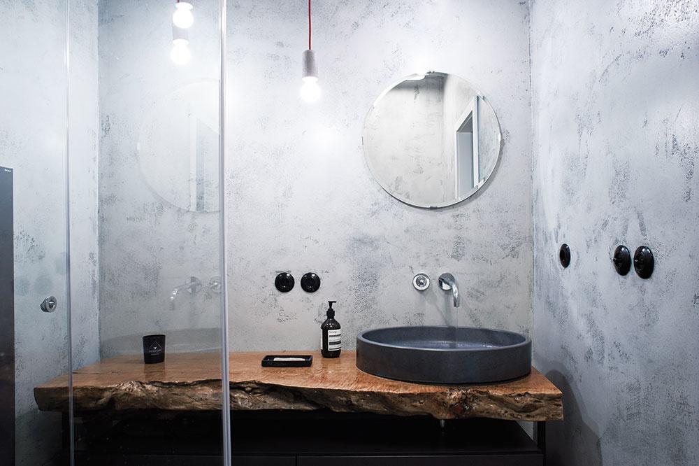 Dve kúpeľne v byte sú zariadené každá v úplne inom duchu. Tej pri rodičovskej spálni dominuje doska z tropického dreva, ktorá kontrastuje s betónovým povrchom stien a antikorovým WC.