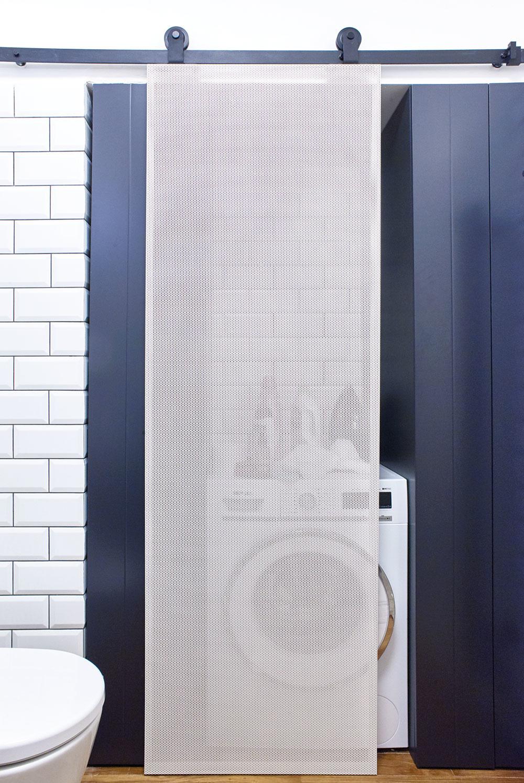 """Súčasťou čierno-bielej kúpeľne je aj nika s vstavanými skriňami a """"minipráčovňou"""" skrytou za posuvnými dvierkami z perforovaného plechu."""