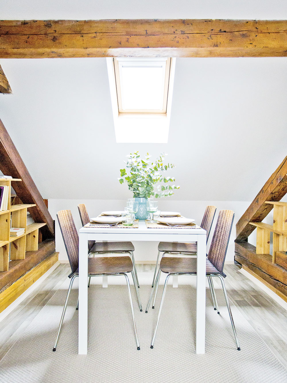 Každá z troch zón bytu má svoj dominantný prvok – v prostrednej je to jedálenský stôl. Priestor medzi drevenými konštrukčnými prvkami krovu bol ako stvorený na umiestnenie políc, ktoré ešte podporili funkčné členenie.