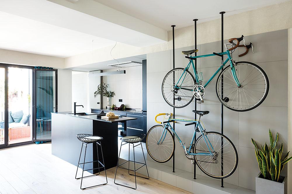 Pri vstupe do bytu je umiestnený originálny stojan na bicykle. Aby sa stena za čiernou konštrukciou neušpinila, navrhli tu architekti sivý obklad, ktorý plynulo prechádza do svetlejšej farebnosti použitej v kuchyni a kúpeľni.