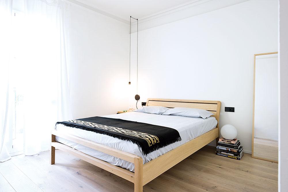 Kúzlo bytu spočíva v čistote riešenia a jednoduchosti jeho zariadenia. Nočný stolík v hlavnej spálni napríklad nahrádza kôpka kníh.