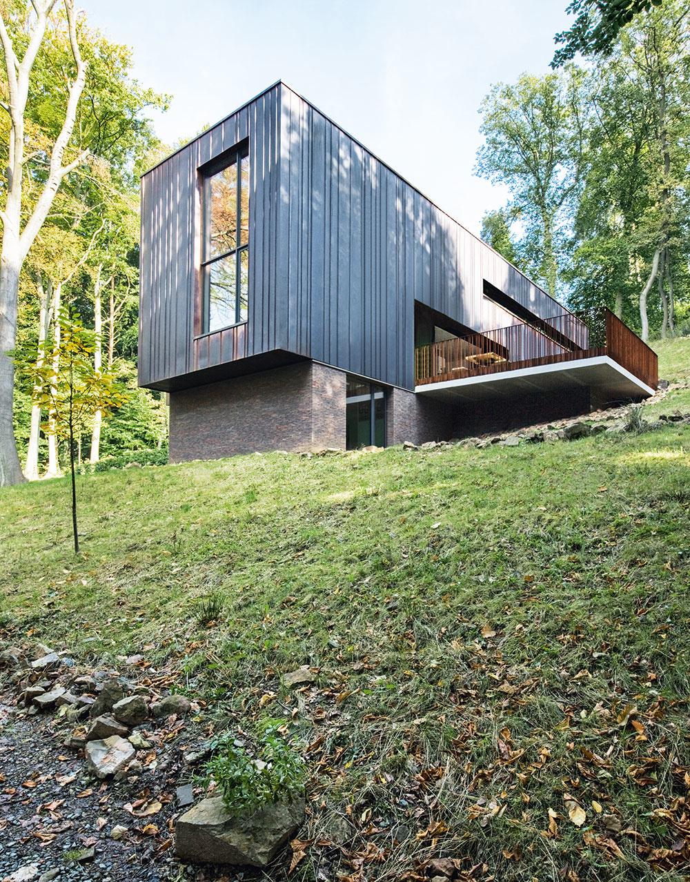 Tehla a meď. Tehlová podnož a medená fasáda s matnou hnedou patinou pôsobia teplým dojmom a ladia s pokojnou farebnosťou okolitého lesa. Tento súzvuk podporujú aj rôzne široké fasádne panely, ktoré vyvárajú prirodzenú nepravidelnú vertikálnu štruktúru podobne ako kmene stromov. (Fasádne konštrukcie zabezpečila rodinná firma J. Gaspard Menuiserie Aluminium, www.gaspard.be.)