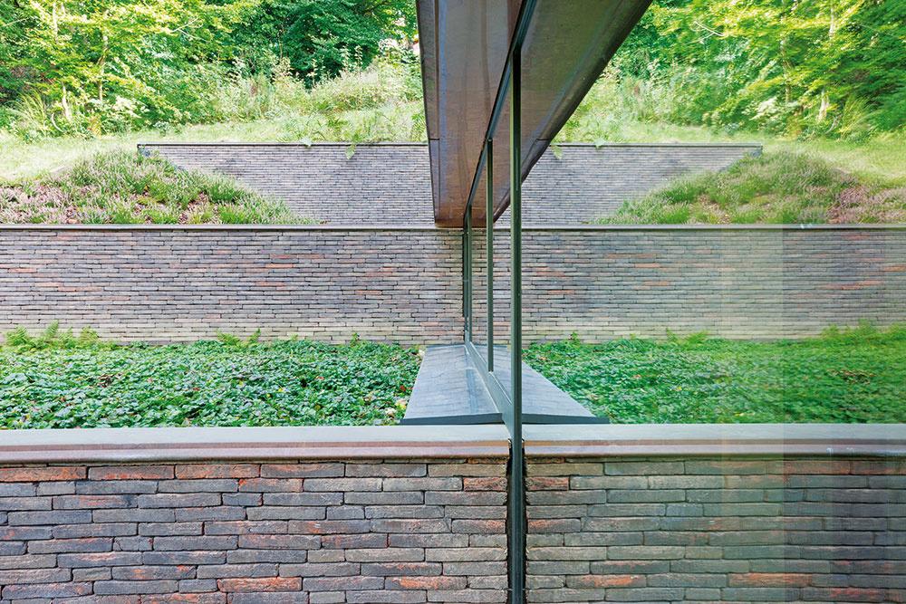 Na severnej strane domu delia stúpajúci terén tehlové oporné múry, s ktorými korešponduje aj členenie fasády.