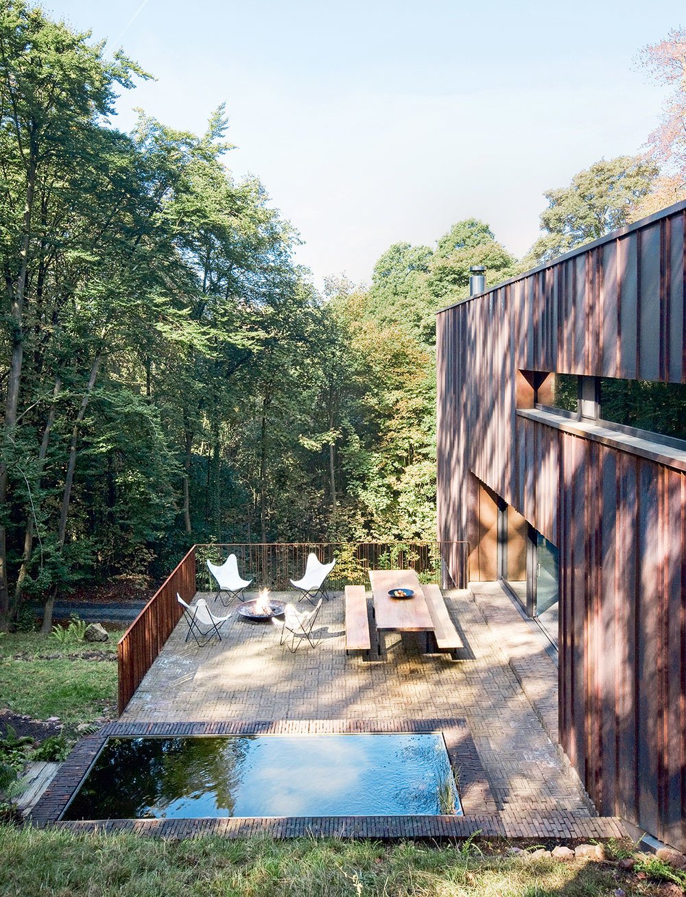 Južnej strane domu dominuje veľká terasa. Intenzívny kontakt s interiérom zabezpečuje veľkoformátová posuvná zasklená stena – hlavný obytný priestor na prízemí sa tým príjemne rozširuje a spája s očarujúcim okolím. (Všetky zasklené konštrukcie a systémy sú hliníkové od firmy Schüco, www.schueco.com.)