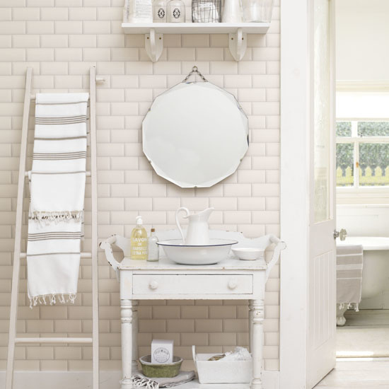 White bathroom with period features.  White tiled walls, vinyl flooring, small white French style tray table with vintage wash bowl and jug, wooden ladder used as towel rail, antique round mirror with chain, shelf containing glass bottles and toiletries , IH 07/2012