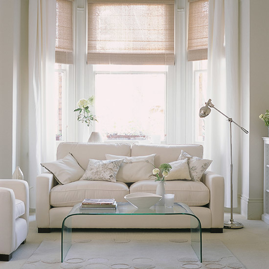 All shades of white livingroom. Pale linen. sofa, clear glass coffee table, Mixed textured cushion covers.  Chrome floor lamp.