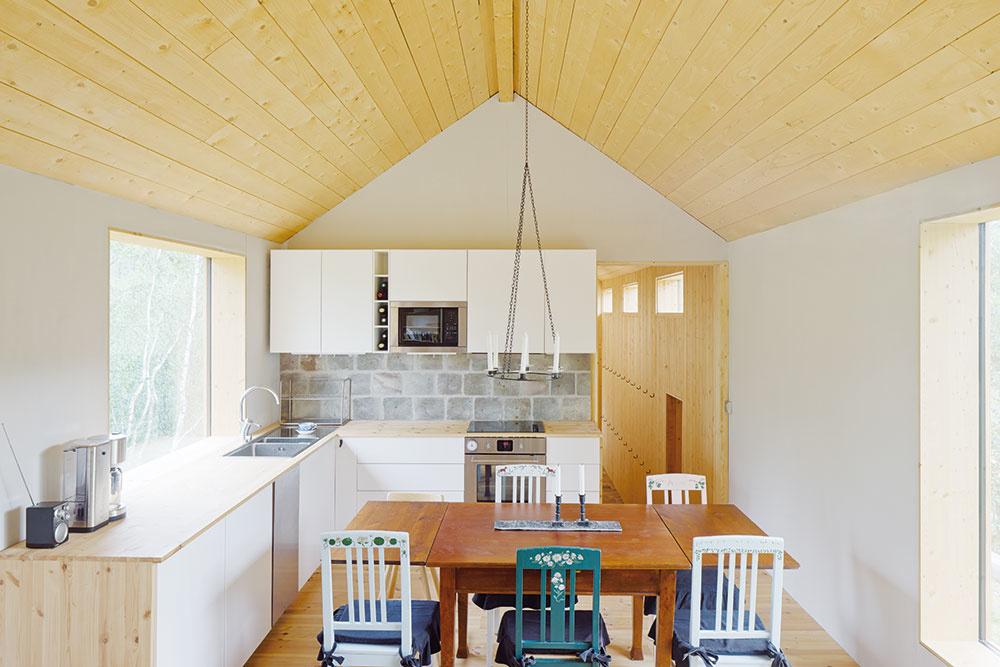 Spoločenský priestor skuchyňou ajedálňou je vo vyššie položenej časti chaty, kde je interiér otvorený až po strechu. Práve tu sú umiestnené veľké okná, stierajúce hranice medzi interiérom aexteriérom, privádzajúce dnu svetlo, ktoré je vmodernej škandinávskej architektúre mimoriadne dôležité.