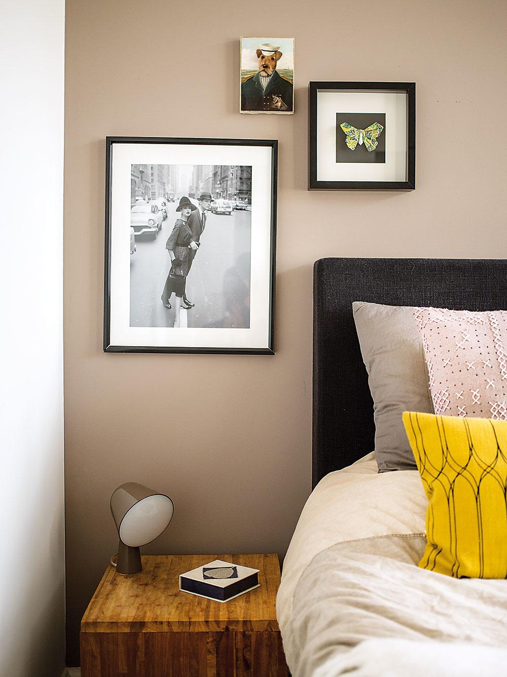 STENA ZA ČELOM POSTELE je natretá béžovou farbou adekorujú ju obrazy afotografie včiernych rámoch. Ale aby to zas nebola až príliš nuda, pokojný charakter miestnosti rozbíja žiarivý žltý vankúš.