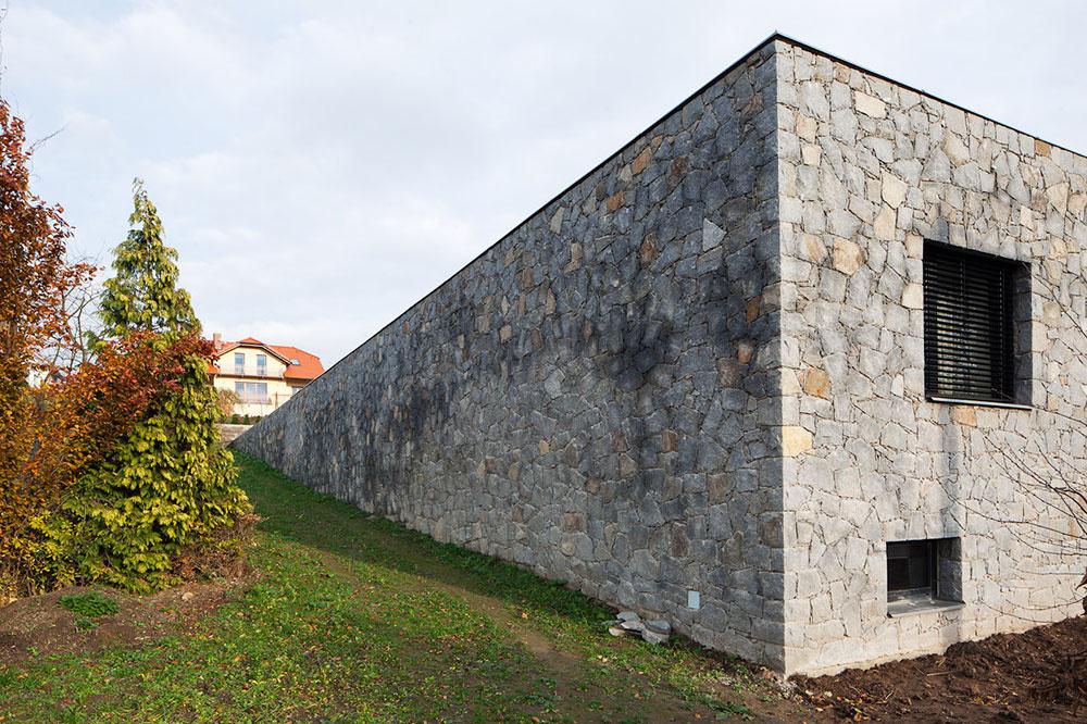 Átriový rodinný dom so zelenou strechou a kamennou fasádou