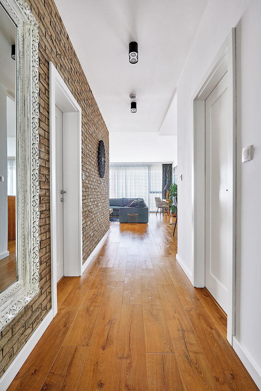 TEHLOVÝ OBKLAD na stene vchodbe rozbíja sterilitu zvyšných bielych plôch na stenách, strope azárubniach adodáva priestoru pocit útulnosti adomáceho tepla.
