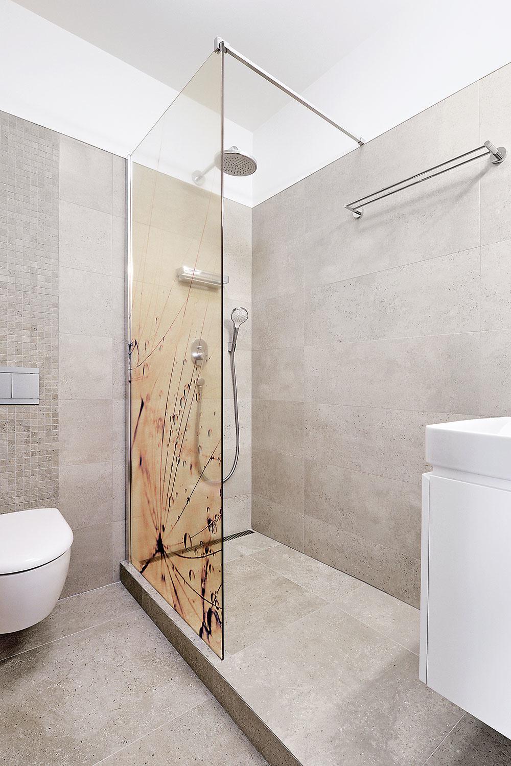 OBKLADY VOBOCH KÚPEĽNIACH, imitujúce kameň, sú od španielskeho výrobcu Porcelanosa. Sprchová zástena vhosťovskej kúpeľni je zo skla sjemným grafickým prírodným motívom, ktoré ozvláštňuje neutrálny obklad.