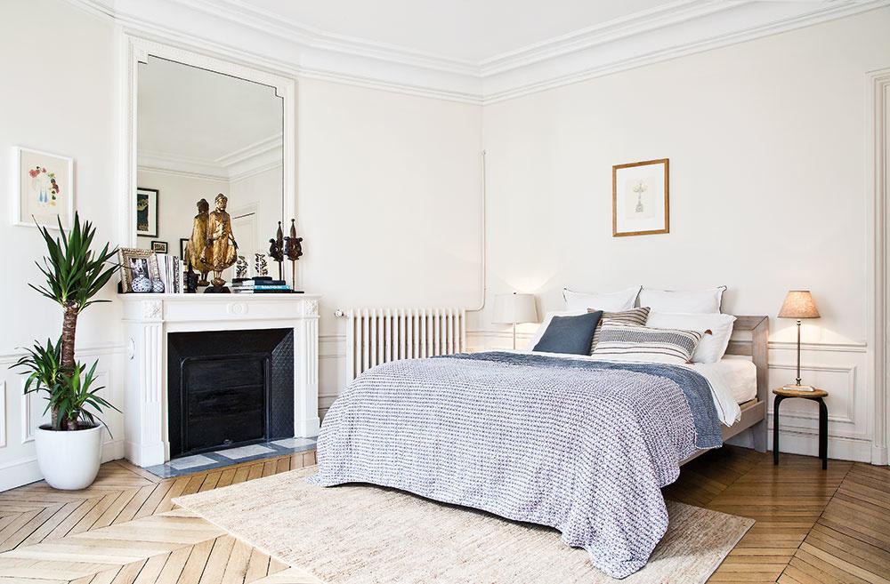 VSPÁLNI okrem postele akozuba nájdete množstvo obrazov, jednoduché nočné stolíky, staršiu komodu azáhradnú stoličku. Útulnosť majiteľ docielil aj textíliami vteplých farbách.