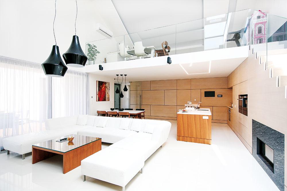 Vo vzdušnom priestore, ktorý je v priamom kontakte s vonkajšou terasou, je situovaná otvorená obývačka spojená  s kuchyňou a jedálňou. Veľkorysá denná zóna zúročuje aj výškové členenie stavby – pod asymetrickou strechou má miesto galéria s pracovňou.