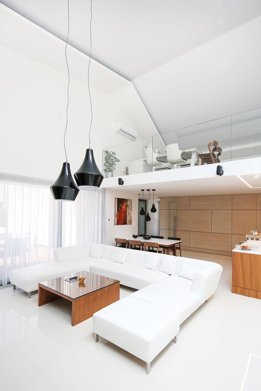 Výrazným prvkom interiéru je kazetový obklad z bielenej dubovej dyhy s čitateľným rastrom, ktorý priebežne prechádza zo vstupnej časti domu až do dennej zóny. Vysoký denný priestor využil architekt na umiestnenie otvorenej galérie s pracovňou.