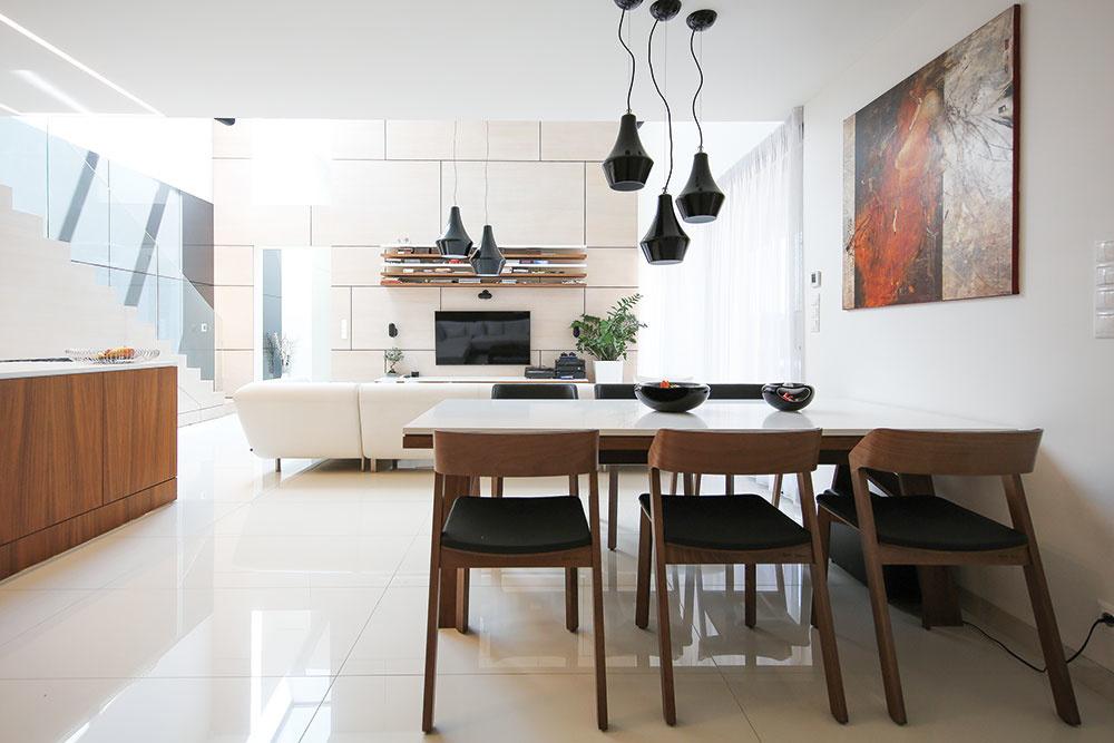V čistom interiéri s bielym základom vynikajú atypické nábytkové prvky vyrobené na mieru a solitéry s elegantným dizajnom. (Jedálenské stoličky Merano od značky Ton, sedačka Brik.)