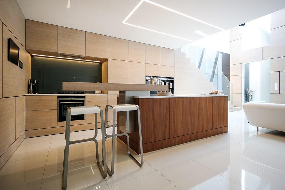 Kuchyňa a jedáleň sú umiestnené v nižšej časti denného priestoru, pod galériou. Blok zabudovanej linky, ktorý vytvára dojem plynulého pokračovania steny obloženej bieleným dubovým drevom, dopĺňa kuchynský ostrov s povrchom z orechovej dyhy. (Barové stoličky LaPalma, dizajn Fabio Bortolani.)