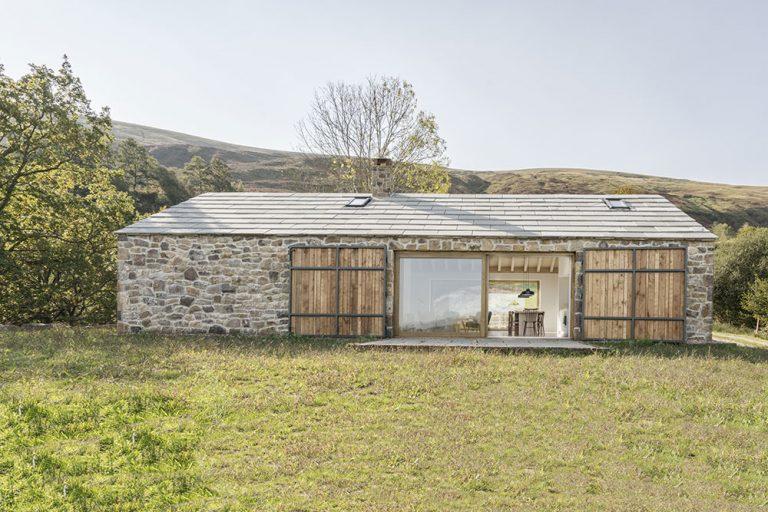 Pasívny dom s kamennou fasádou a veľkými preskleniami vyrástol z totálnych ruín
