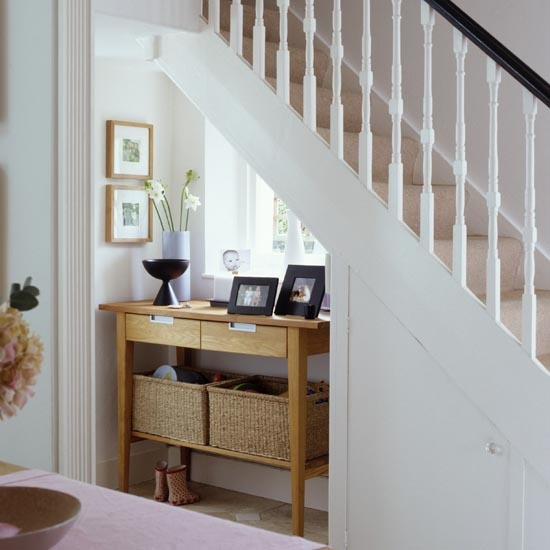 Console table under stairs, staircase, banister, wicker basket, real home. Pub orig IH 04/2007
