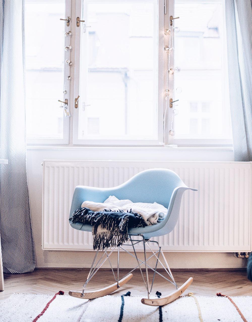 Hojdacie kreslo umiestnené pod veľkými oknami poskytuje dokonalý priestor na relax.