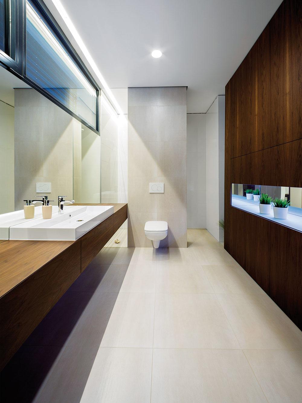 Vrodičovskej kúpeľni sa rovnako ako vcelom interiéri uplatnili prírodné materiály vich prirodzenej podobe. Architekti ich skombinovali smonochromatickými farbami – bielou aantracitovou.