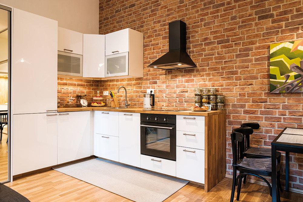 Staré snovým. Biela lesklá kuchyňa zIKEY tvorí príjemný kontrast stehlovou stenou astoličkami zdruhej ruky.