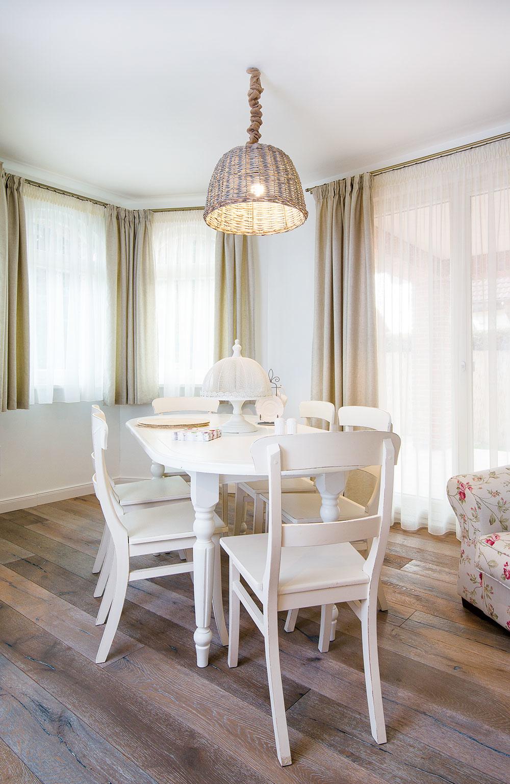 PRESVETLENÁ JEDÁLEŇ s masívnym stolom priam nabáda k tomu, aby ste sa usadili a vychutnali si veľkorysé stolovanie, ako sa patrí. Záclony a závesy sú v celom dome šité na mieru, aby ladili so zvyšným zariadením.