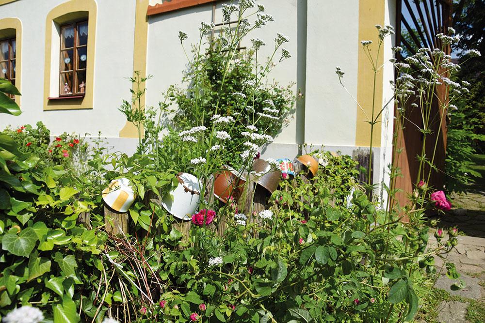 Ako zrozprávky. Domáci nenechávajú nič na náhodu. Vidiecky štýl je viditeľný už vpredzáhradke, kde okoloidúcich potešia farebné hrnčeky aobité hrnce. Za plotom si nerušene rastú tradičné trvalky amnožstvo osvedčených druhov byliniek.