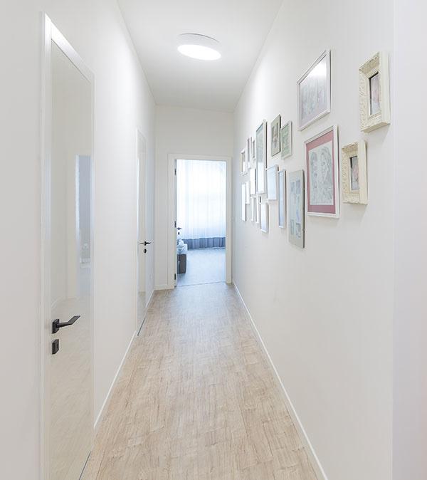 Rodinné fotografie zmenili chodbu vedúcu krodičovskej spálni na malú galériu. Na tom, že pôsobí príjemne, majú svoj podiel aj svietidlá, ktoré dávajú silné biele svetlo podobné dennému, atiež svetlé farby všetkých povrchov vrátane dverí, ktoré robia priestor vzdušnejším.