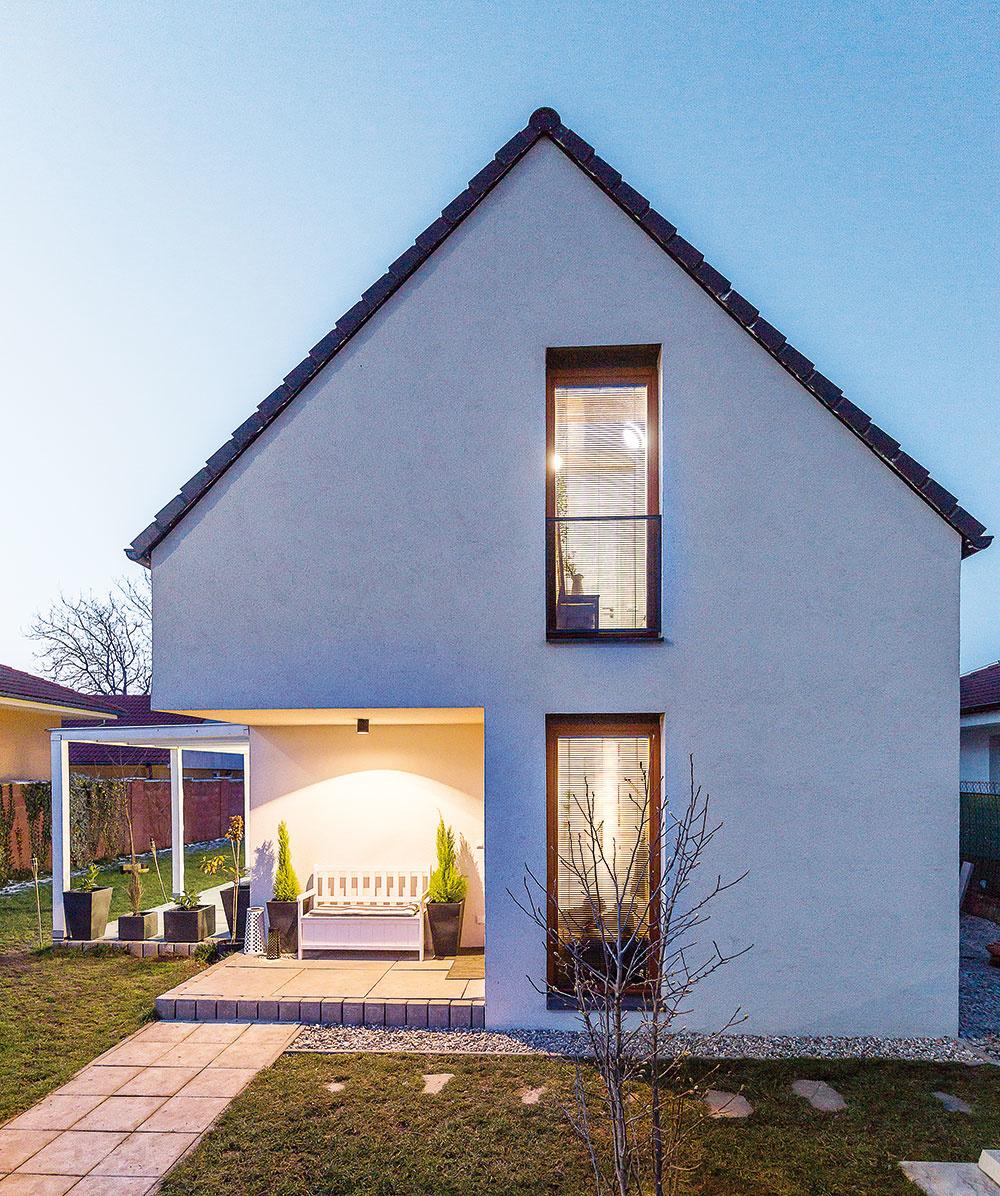 Tradičnú siluetu domu doplnila dvojica autorov niekoľkými súčasnými prvkami. Zahĺbenie vuličnej fasáde vytvára praktické prekrytie priestoru pred vstupom, hmotovo ho vyvažuje terasa svystupujúcim zastrešením.